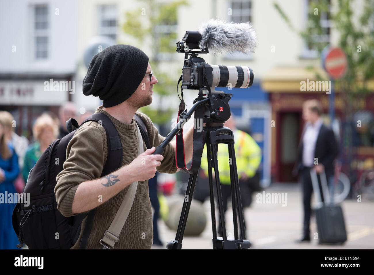 A cameraman filming at an outdoor event in Warwick using a digital SLR camera on a tripod - Stock Image