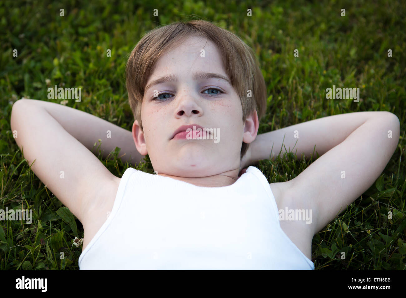 Boy lying on the grass with his hands behind his head - Stock Image