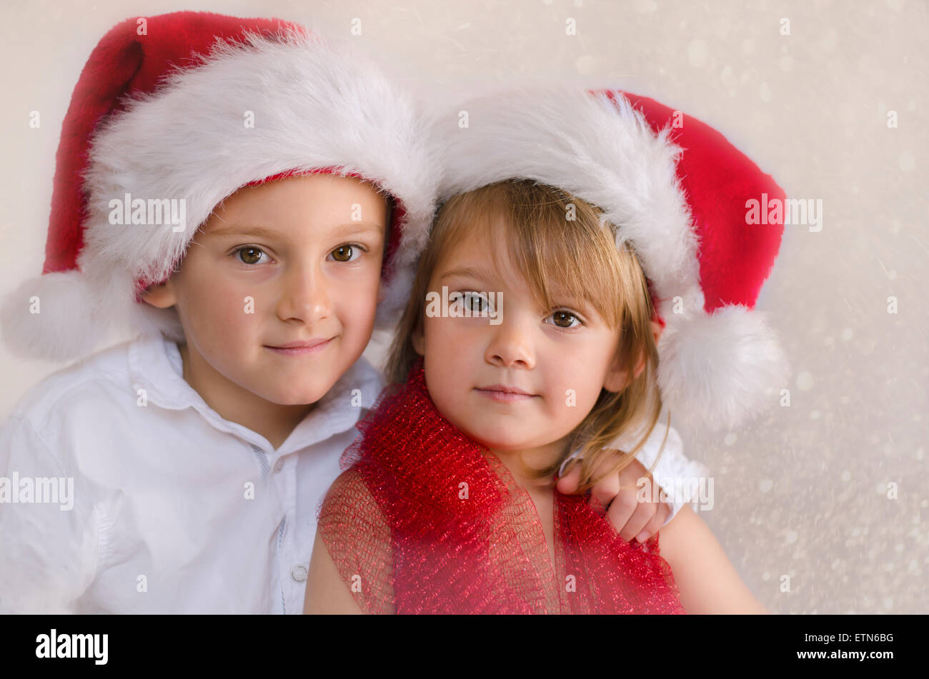 Portrait of two children in Christmas hats - Stock Image