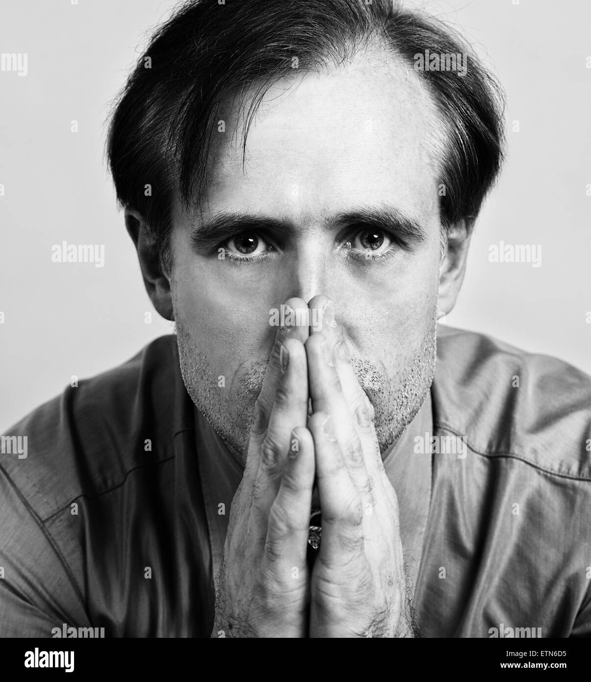 Close-up portrait of a mid adult man with his hands in front of his mouth - Stock Image