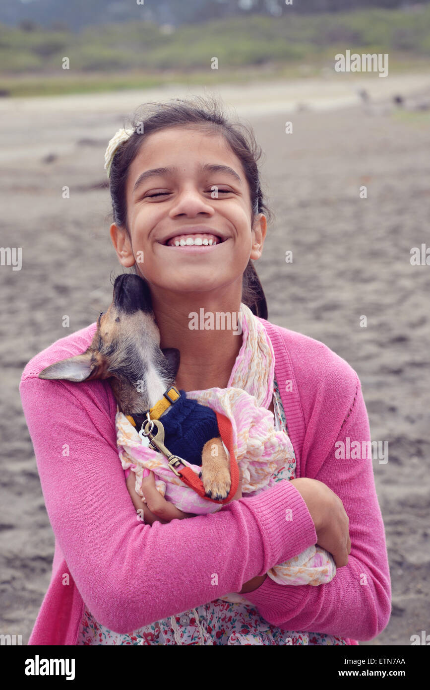 Smiling girl cuddling a puppy - Stock Image