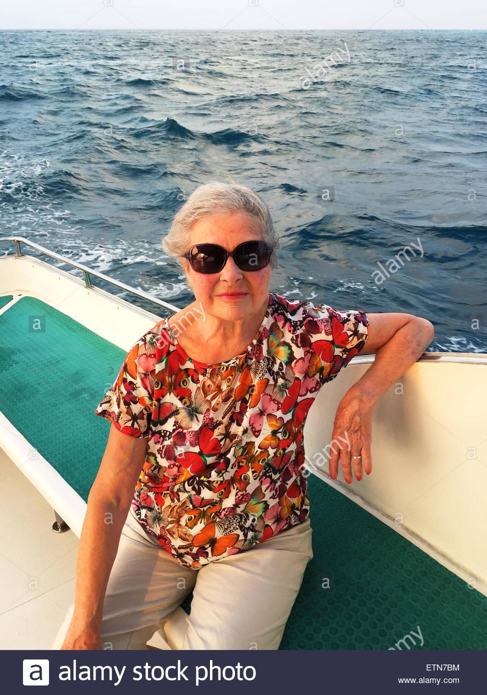 Portrait of a senior woman sitting on boat, Maldives - Stock Image