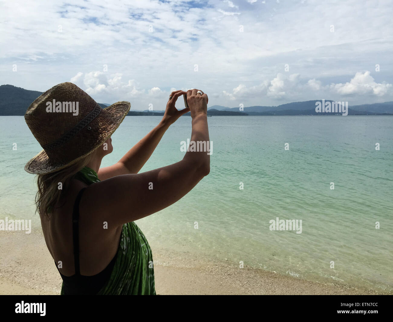 Woman on beach taking a photo - Stock Image