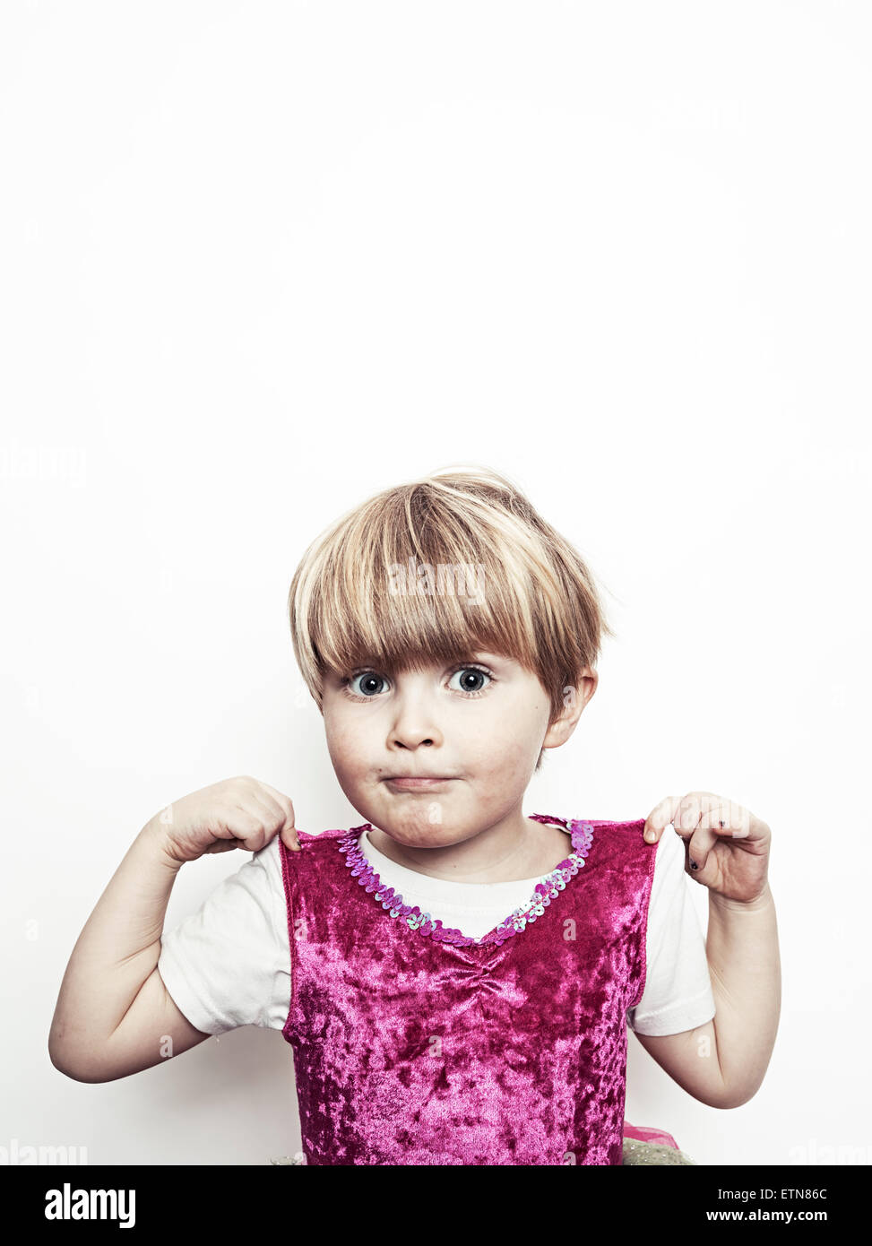 Boy showing off his pink shirt - Stock Image