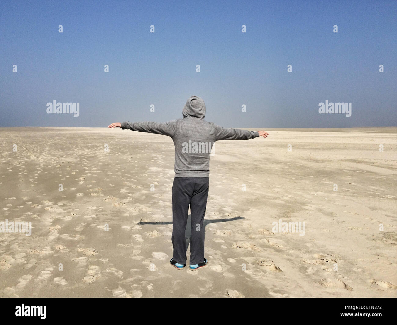 Rear view of a man with outstretched arms on a beach, Denmark - Stock Image