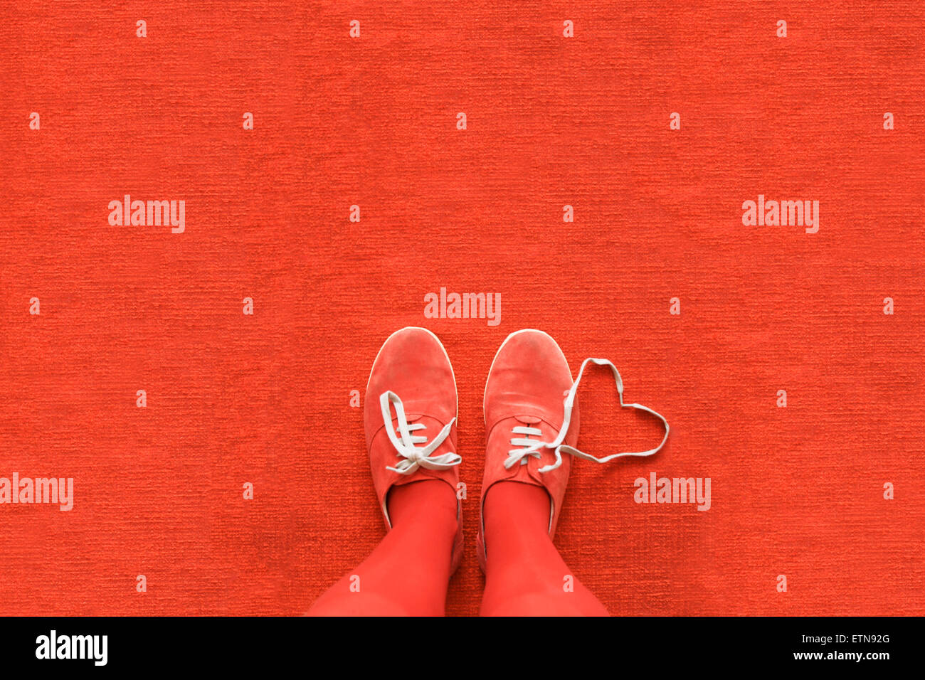 Knees down view of a woman's legs with a heart made out her shoelaces - Stock Image