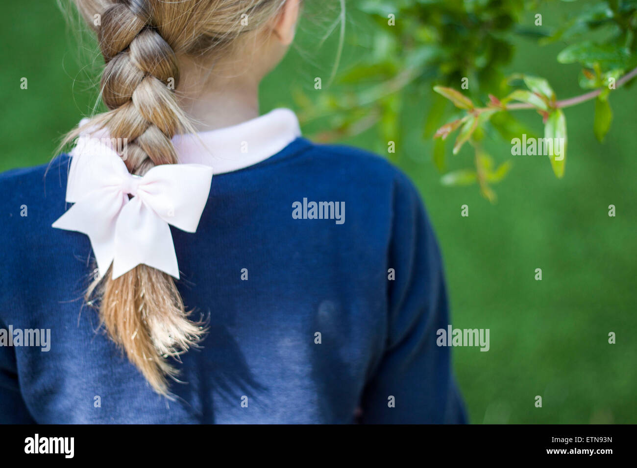 Rear view of a girl with a braid - Stock Image