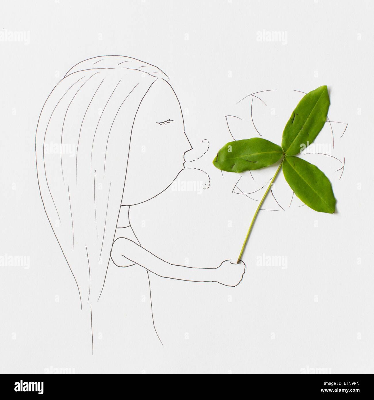 Conceptual girl blowing a pinwheel - Stock Image