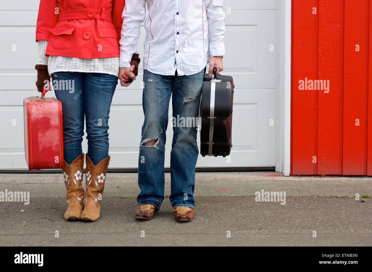 Low section of couple holding a suitcase and guitar case - Stock Image
