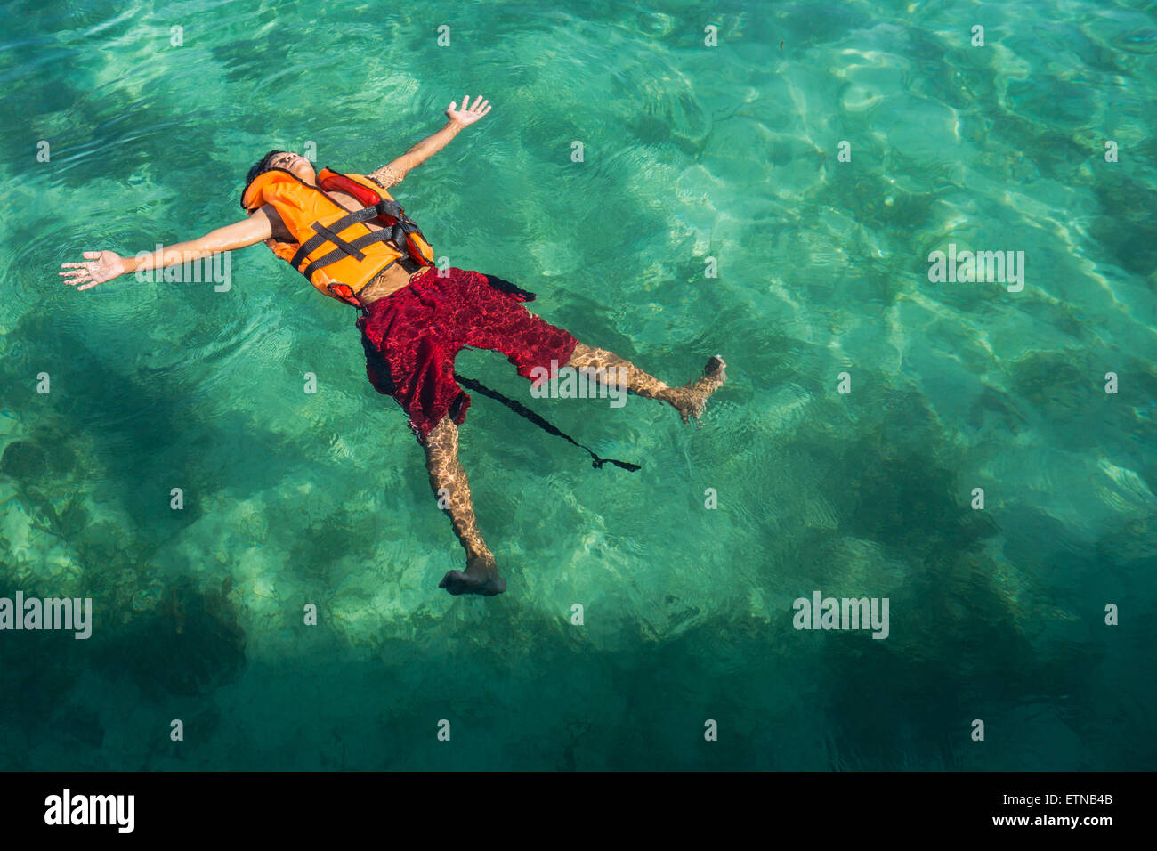 Teenage boy wearing a life jacket, floating in the sea, Salakan Island, Semporna, Sabah, Malaysia - Stock Image