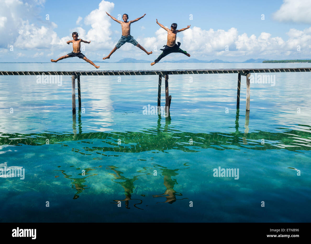 Three boys jumping in to the sea from a jetty, Salakan Island, Semporna, Sabah, Malaysia - Stock Image
