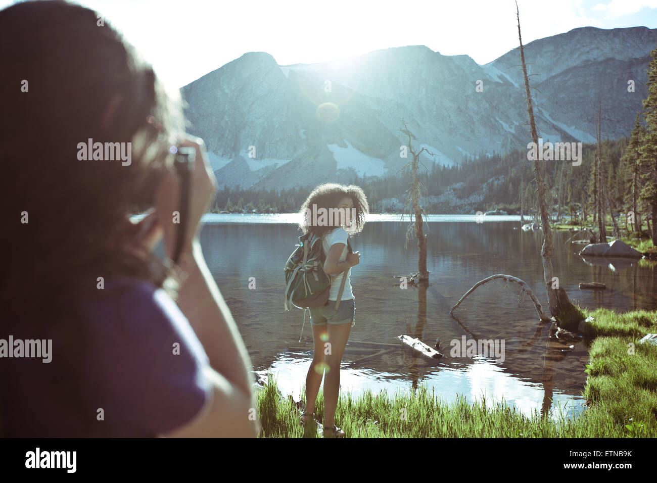 Woman taking a photo of another woman standing by a lake, Wyoming, USA - Stock Image
