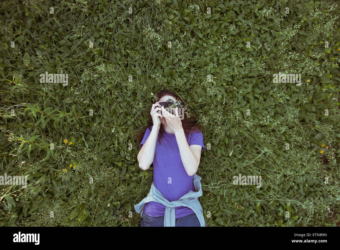 woman lying in grass photographing sky - Stock Image