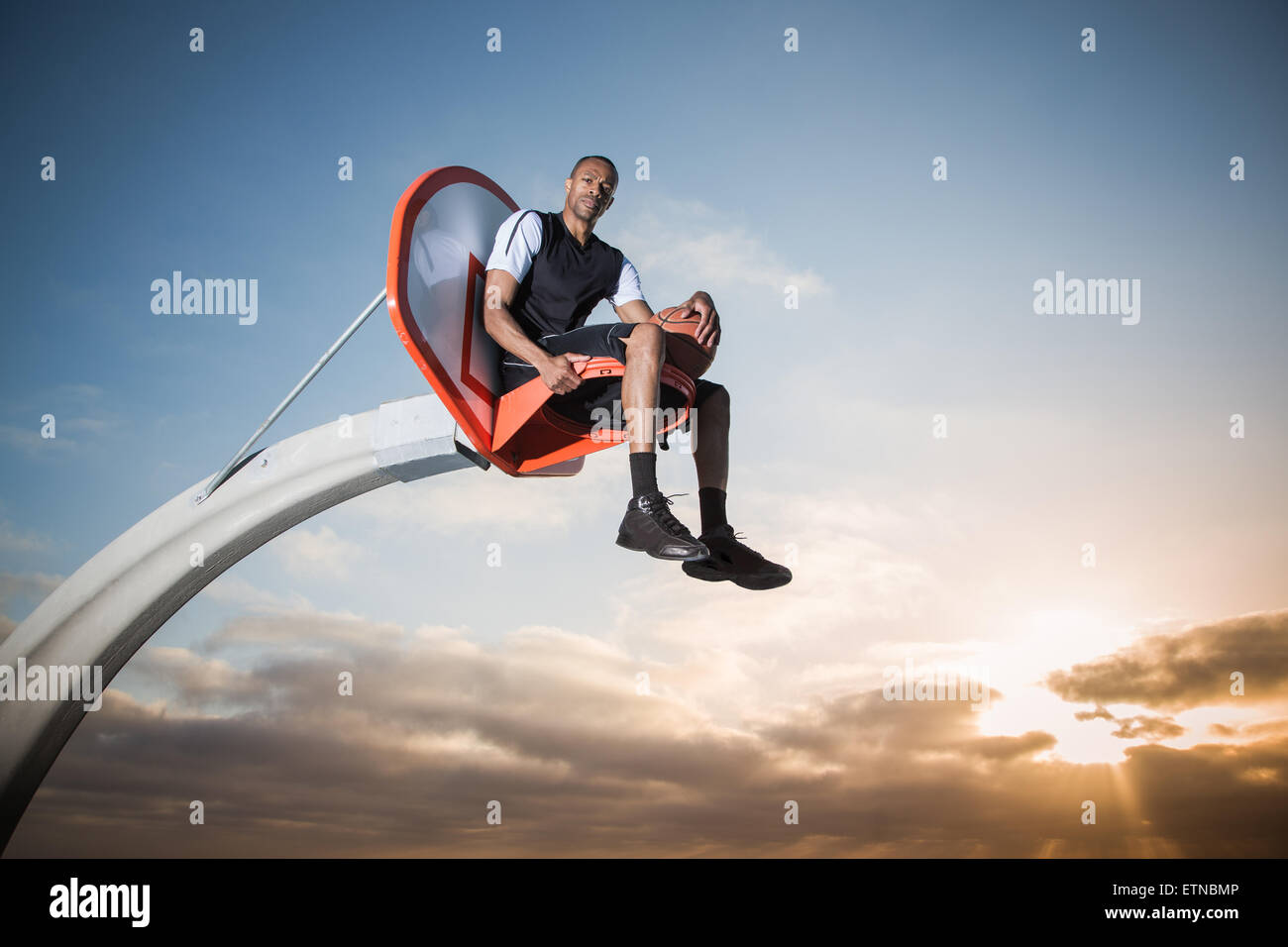 Portrait of a young man sitting in a basketball hoop in a park, Los Angeles, California, USA Stock Photo