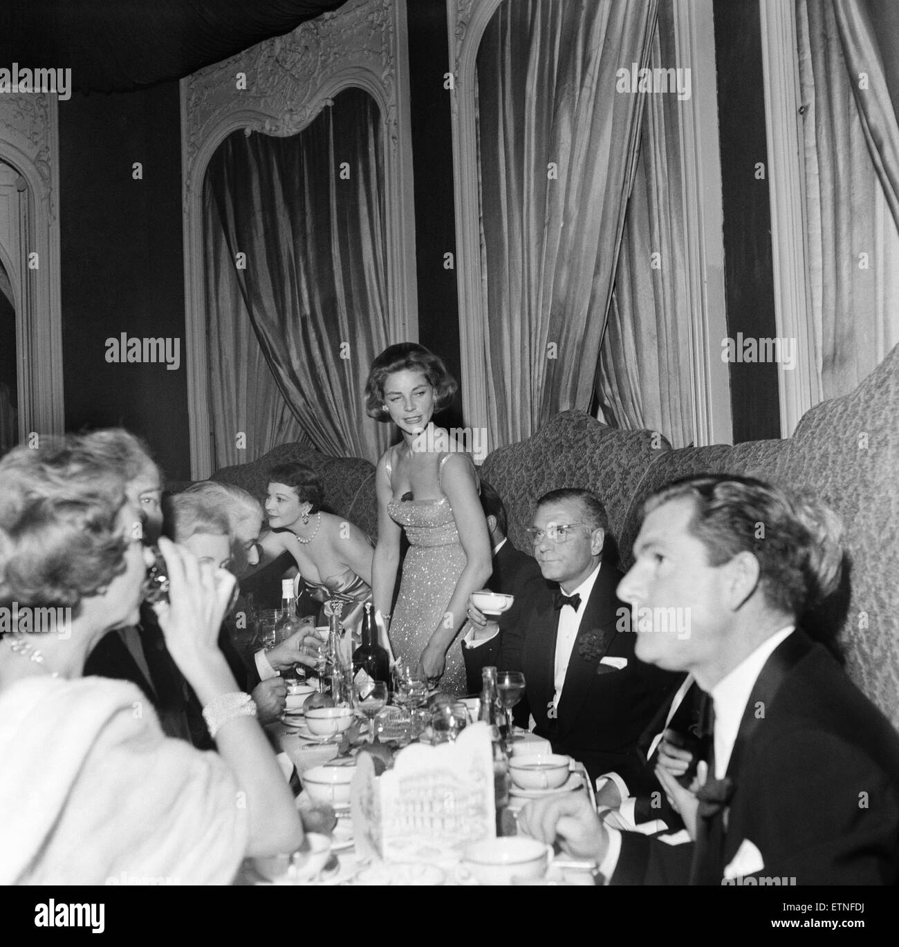 Guests attending a party held by Laurence Olivier and Lauren Bacall. Lauren Bacall about to sit down, with guests - Stock Image