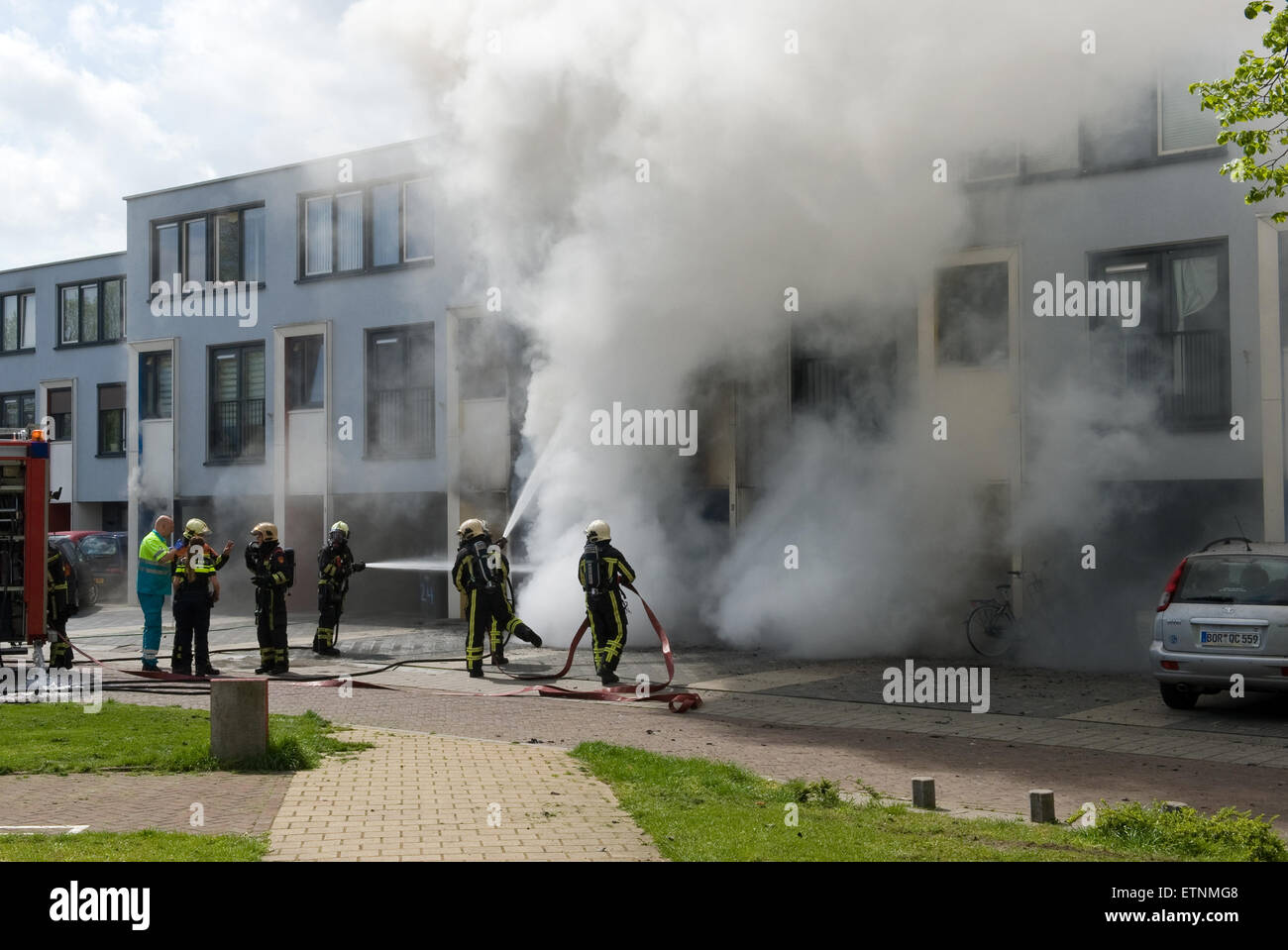 ENSCHEDE, THE NETHERLANDS - 07 MAY, 2015: Firefighters are busy to extinguish a fire in a house - Stock Image
