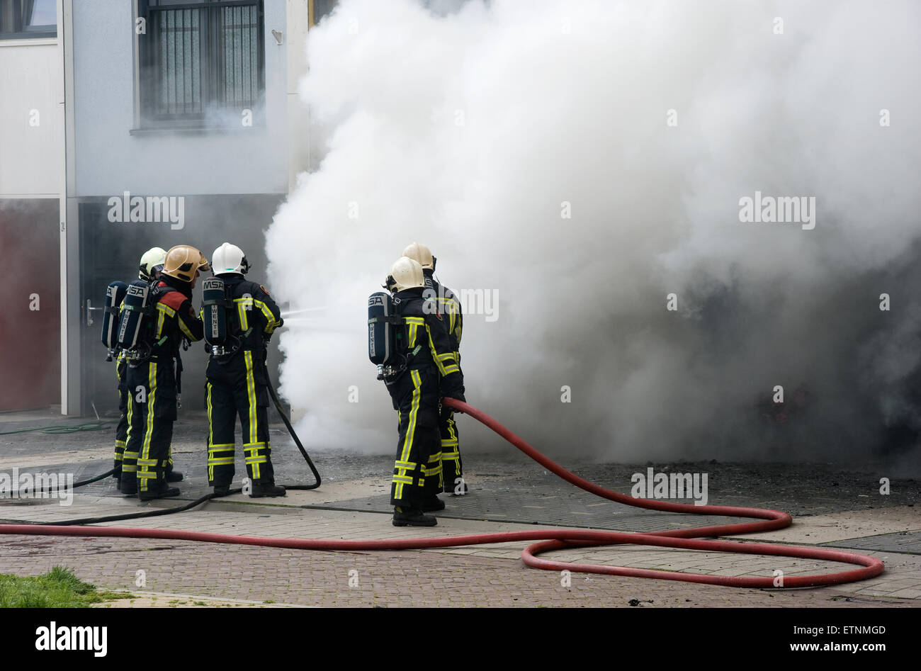 Firefighters are busy to extinguish a fire in a house - Stock Image