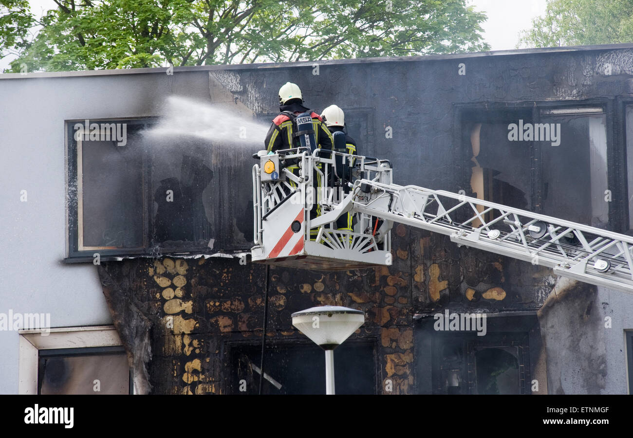 Firefighters are busy to extinguish a fire in a house on a lifting ramp - Stock Image