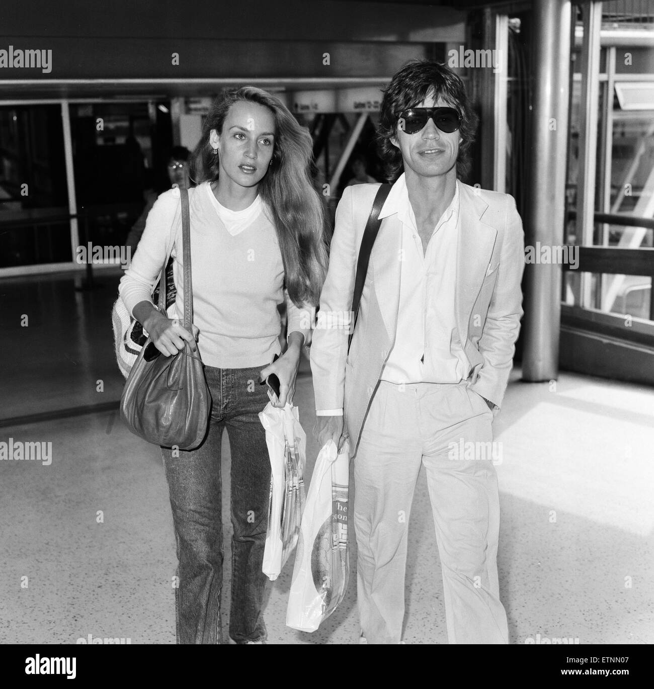 Mick Jagger and girlfriend, model, Jerry Hall, pictured at London Heathrow Airport, departing for India, 28th July Stock Photo