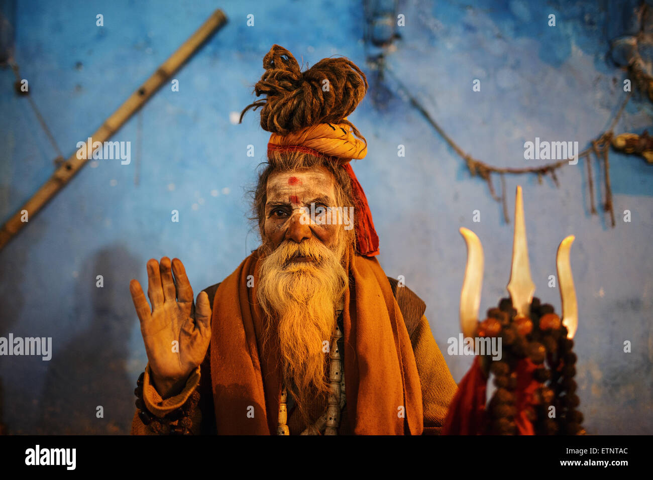 An old bearded man (Sadhu) wearing traditional outfit poses to a photo at night in Varanasi, India. - Stock Image