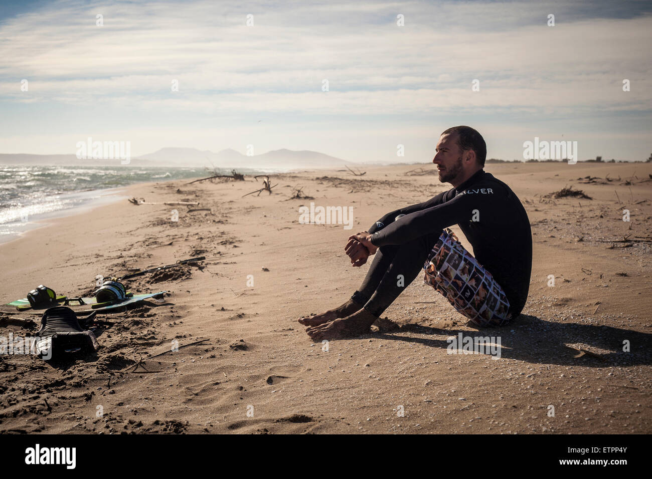 Kite surfer in Wet suit sitting on beach, thoughtful, wistful, beach, costa Brava, girona - Stock Image