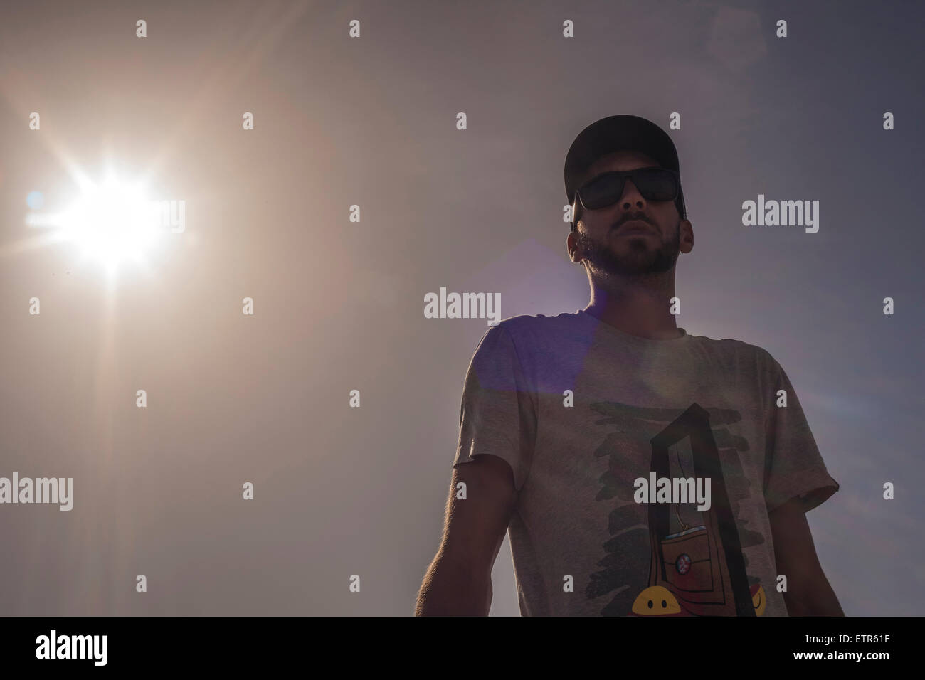 Lifestyle, urban scene, male, young, men, sunglass, observing, facing sunlight, cap, Generation Y - Stock Image