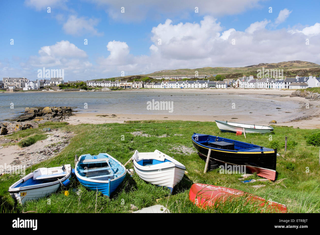 Boats by harbour with view to houses overlooking Leodamais Bay in Islay village of Port Ellen Isle of Islay Inner - Stock Image