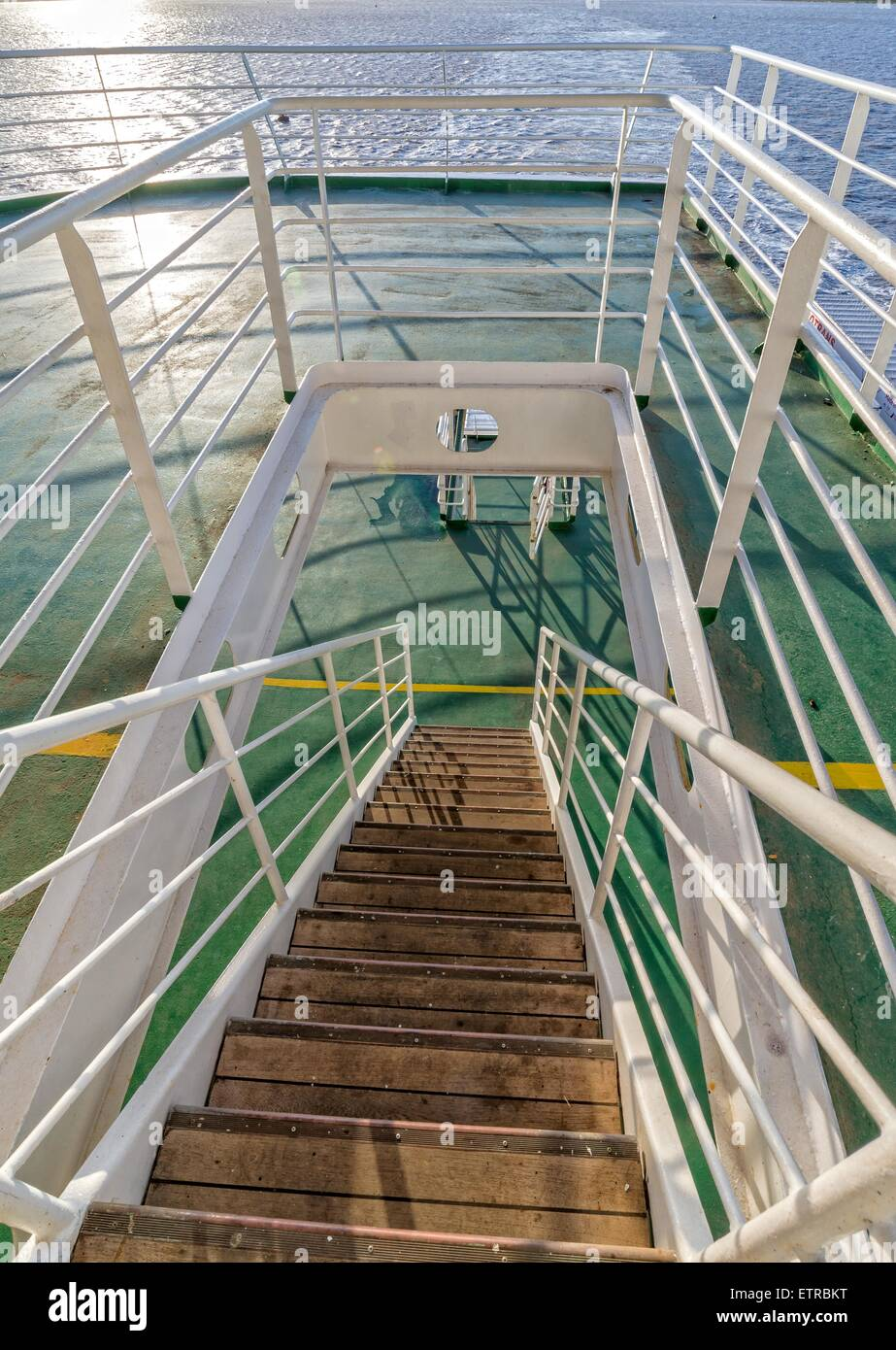 Flights of stairs on board a ship leading down to other decks. - Stock Image