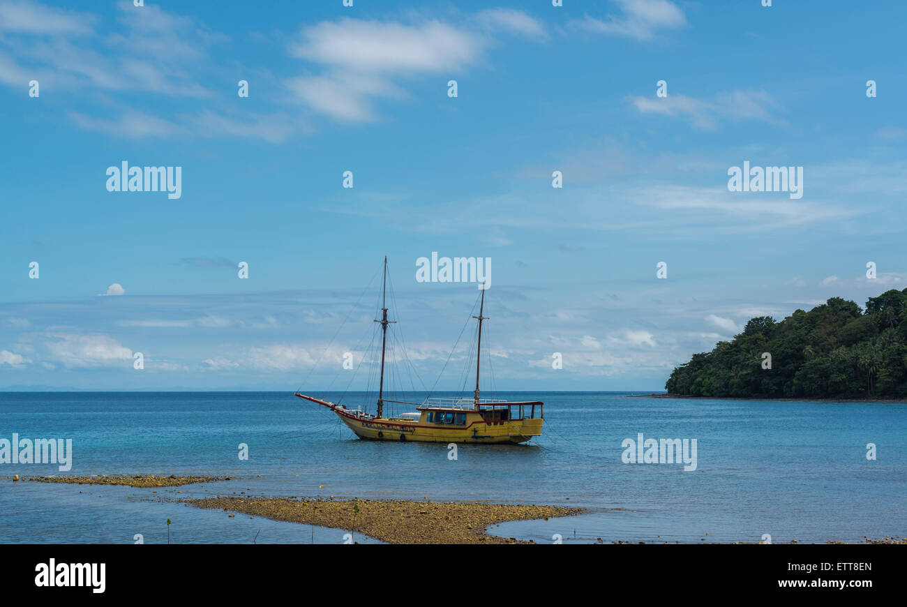 Old wooden sailing boat anchored in a bay at low tide - Stock Image