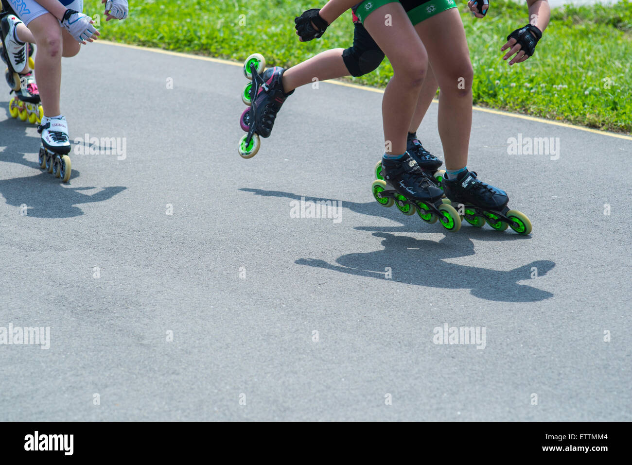 Legs of in-line skaters in speed skates in motion during competitions Stock Photo