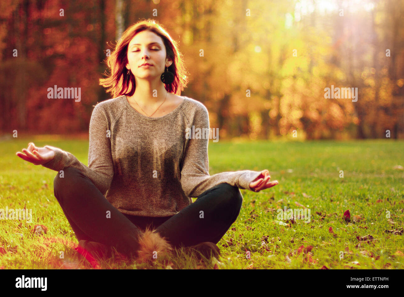 Young attractive female meditate in park. - Stock Image
