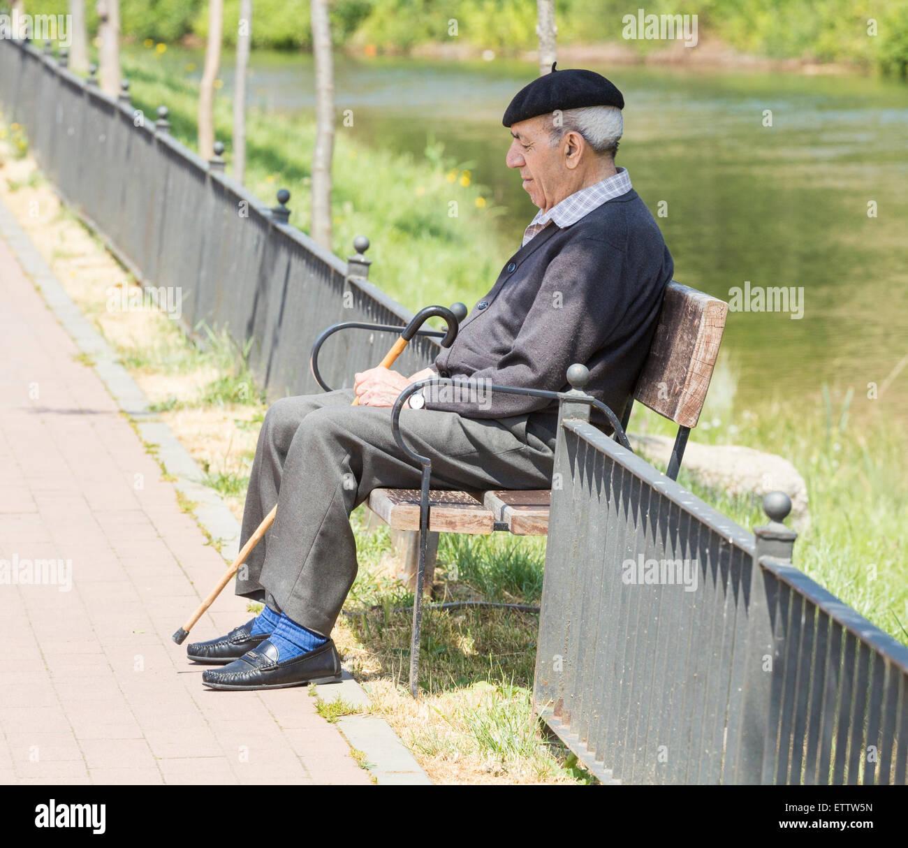 Elderly Spanish man taking siesta on bench near river. Spain - Stock Image