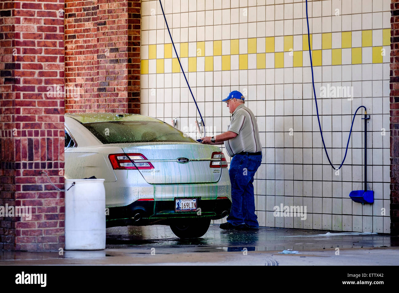 Car wash business stock photos car wash business stock images alamy a senior caucasian man washes his silver car in a coin operated car wash stall in solutioingenieria Images