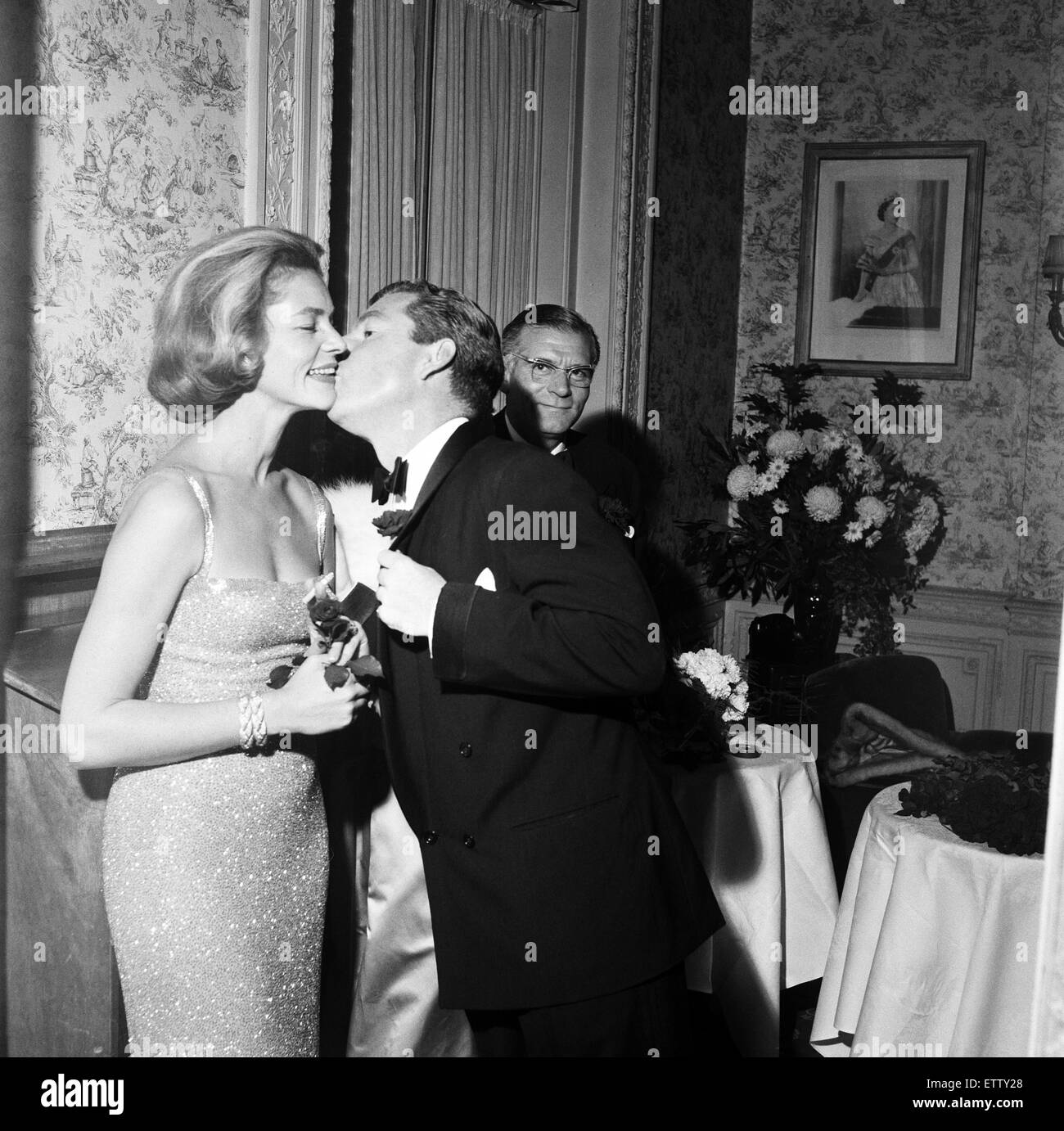Guests attending a party held by Laurence Olivier and Lauren Bacall. Lauren Bacall receiving a kiss on the cheek - Stock Image