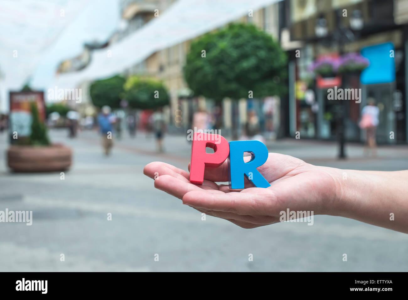 Bulgaria, Hands holding letters PR, pedestrian area - Stock Image