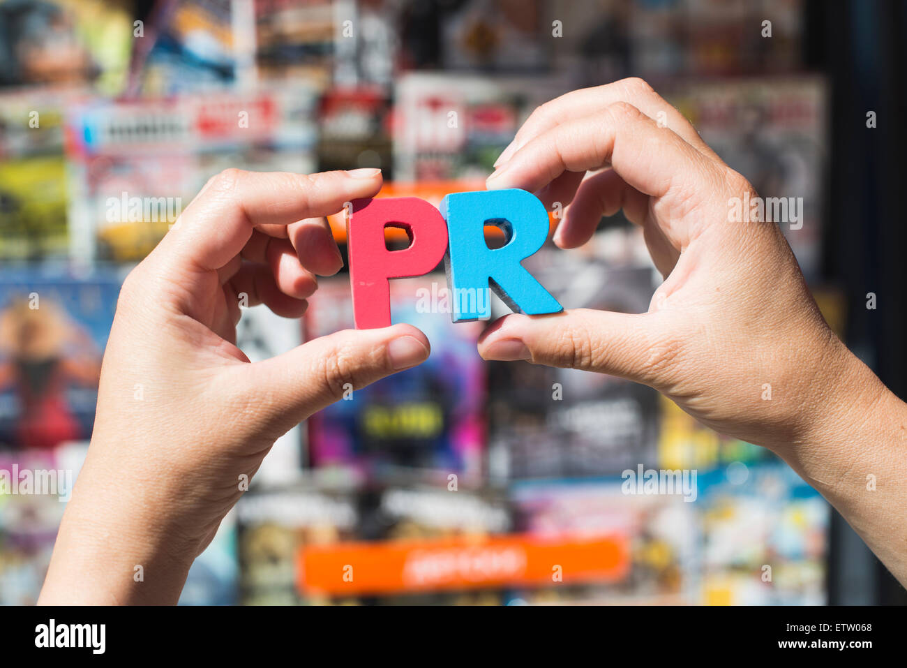 Word PR in front of kiosk for selling newspapers and magazines, hands holding wooden letters - Stock Image
