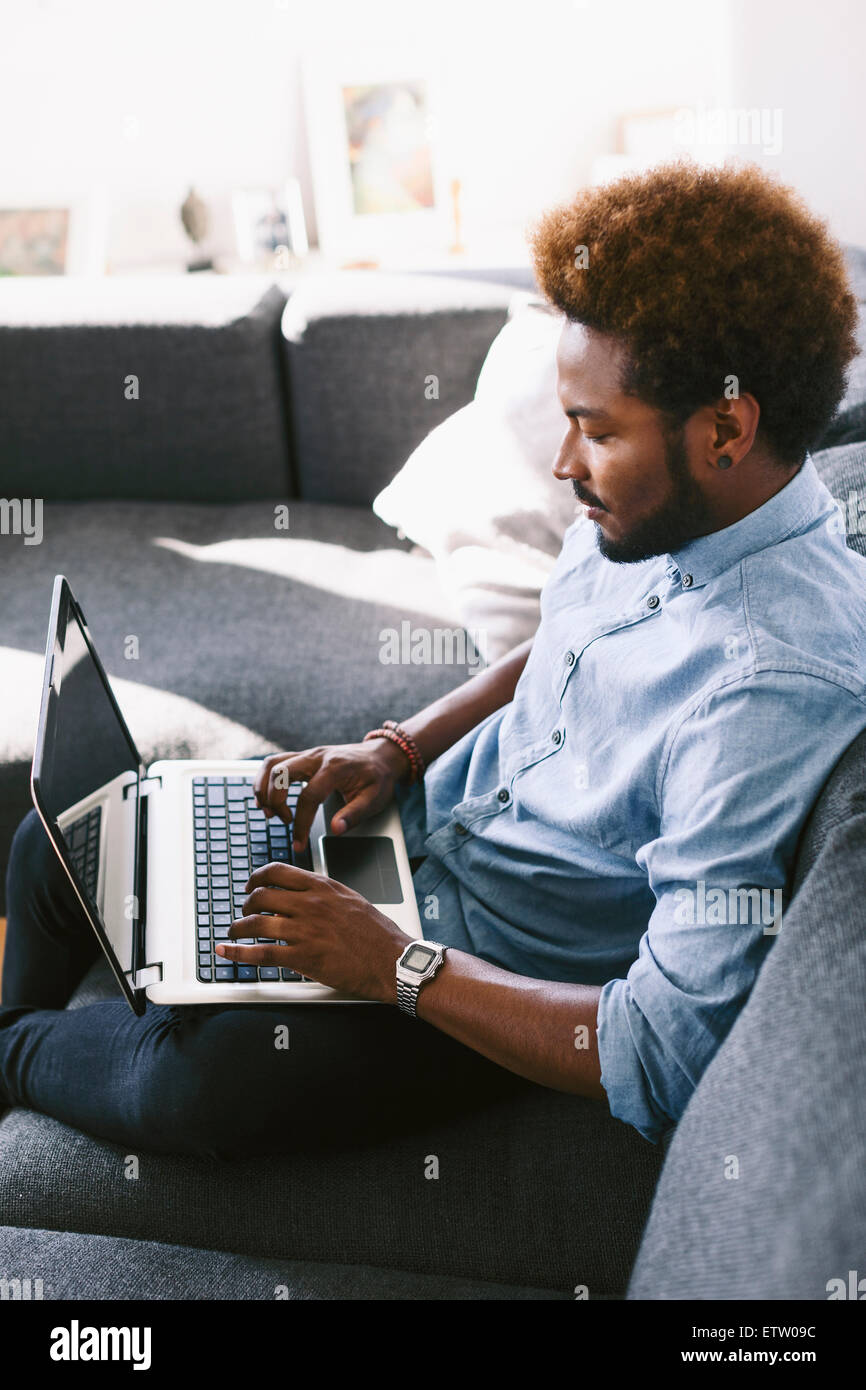 Young Afro American man sitting on couch, using laptop - Stock Image