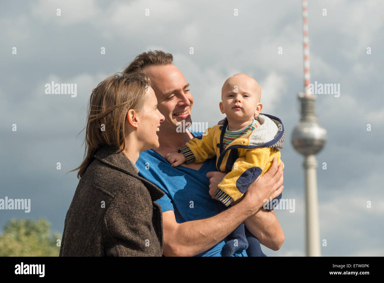 Germany, Berlin, happy couple with baby boy in front of television tower - Stock Image