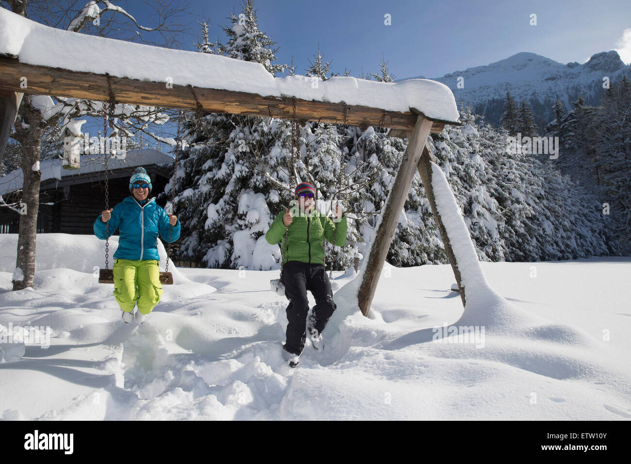 Germany, Bavaria, Inzell, couple sitting on swings in snow-covered landscape Stock Photo