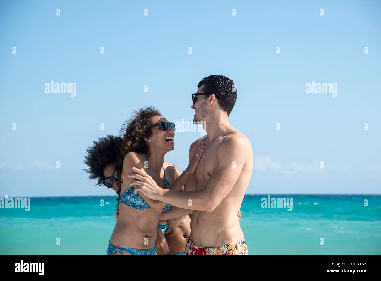 Three people playing on the beach Stock Photo