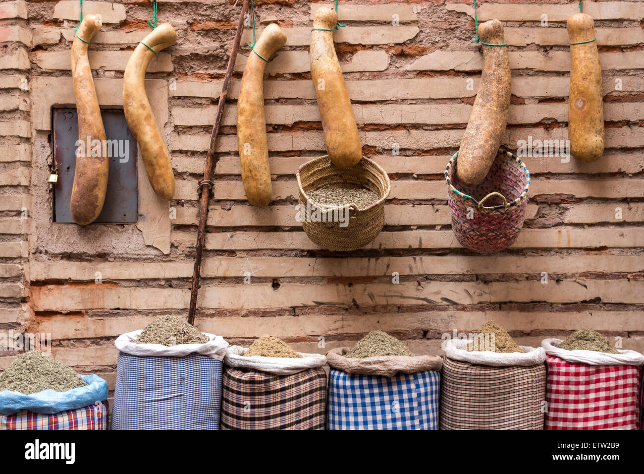 Morocco, Marrakesh, row of calabashes and sacks with spices in front of facade - Stock Image