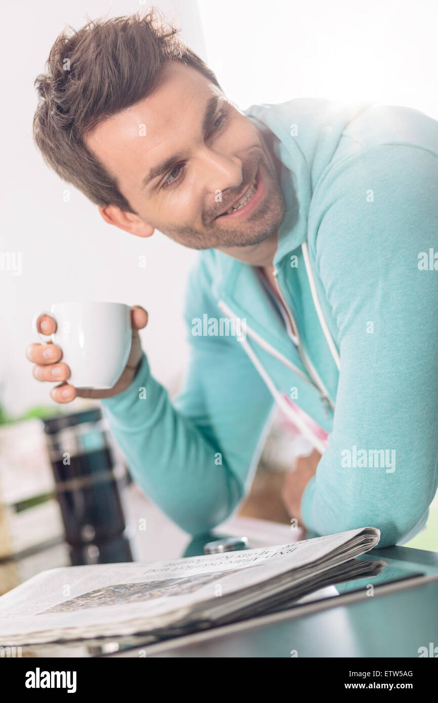 Portrait of man with cup of coffee and newspaper in the kitchen Stock Photo