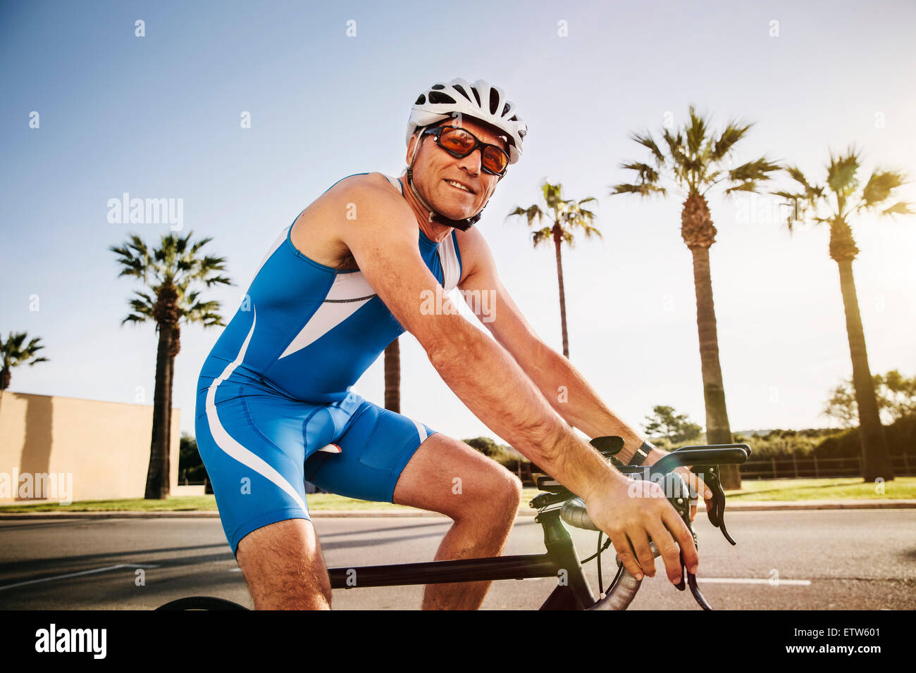 Spain, Mallorca, Sa Coma, smiling triathlet training on bicycle - Stock Image