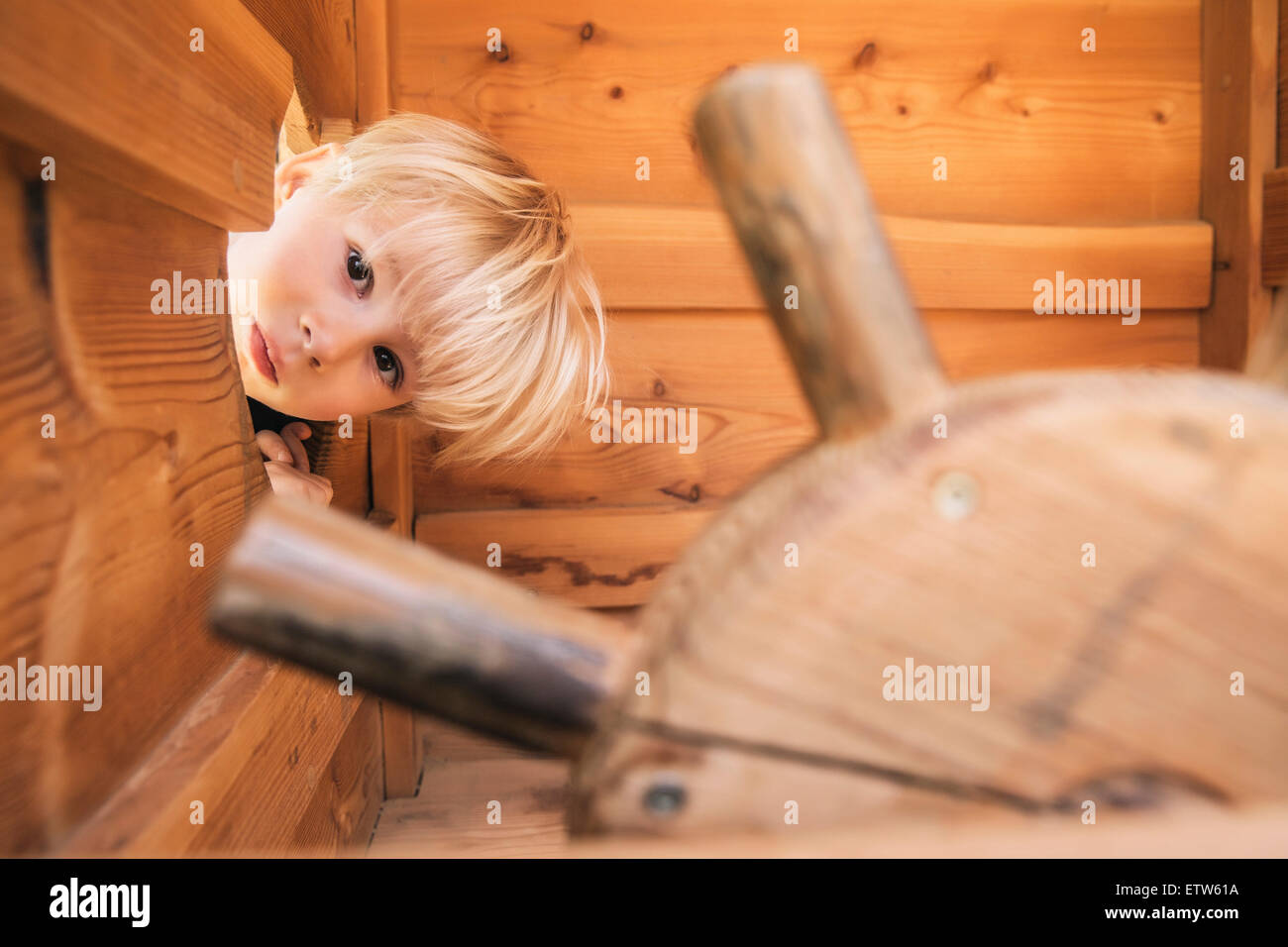 Little boy looking through hole in wooden ship on playground - Stock Image
