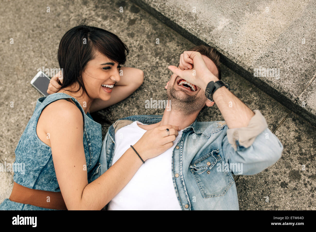 Laughing young couple lying on the ground outside - Stock Image