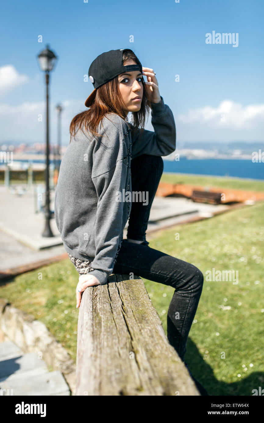 Spain, Gijon, young woman sitting on wooden beam - Stock Image