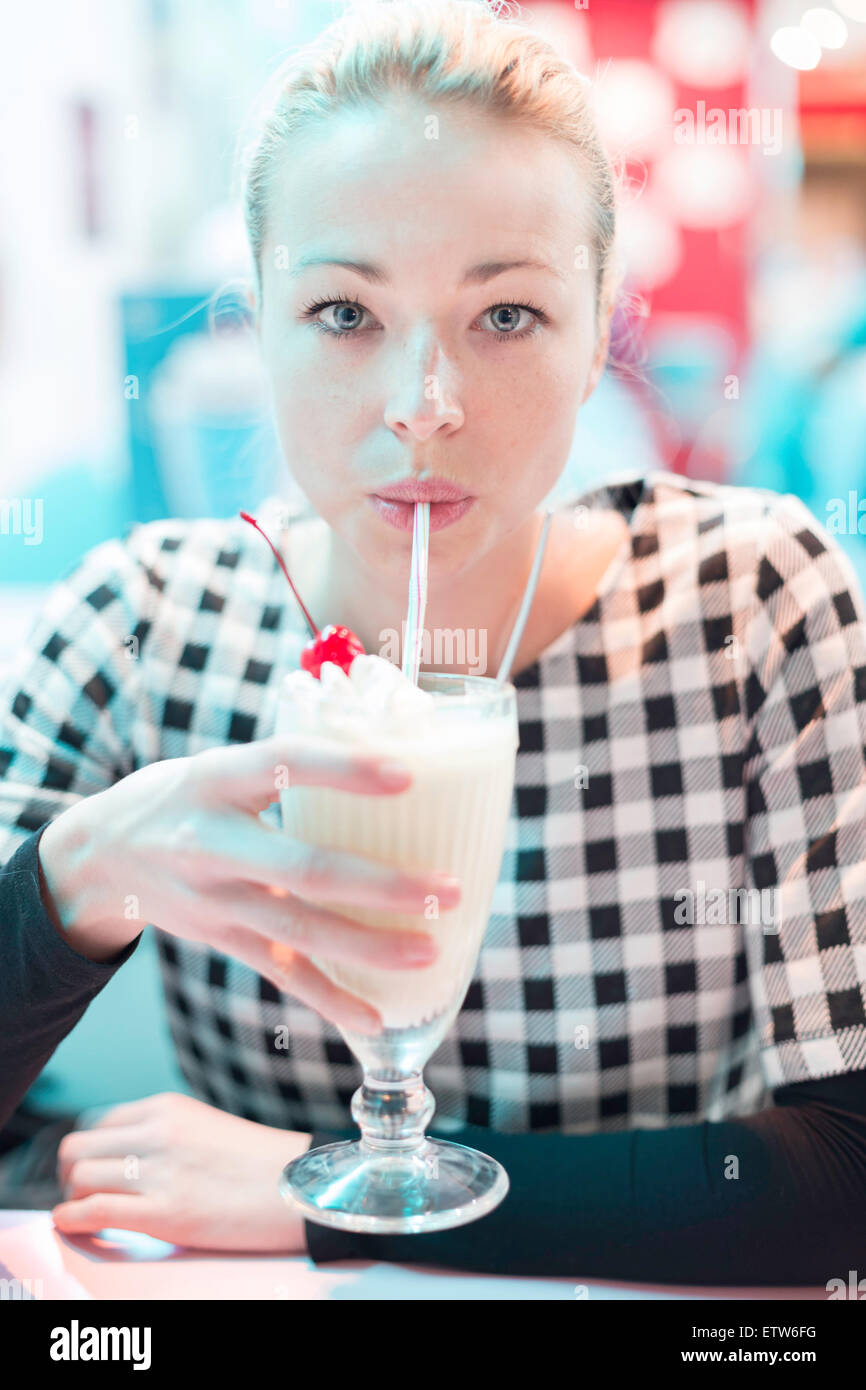Woman drinking milk shake in diner. - Stock Image