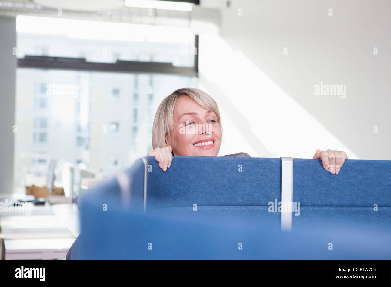 Businesswoman looking over partition in office - Stock Image