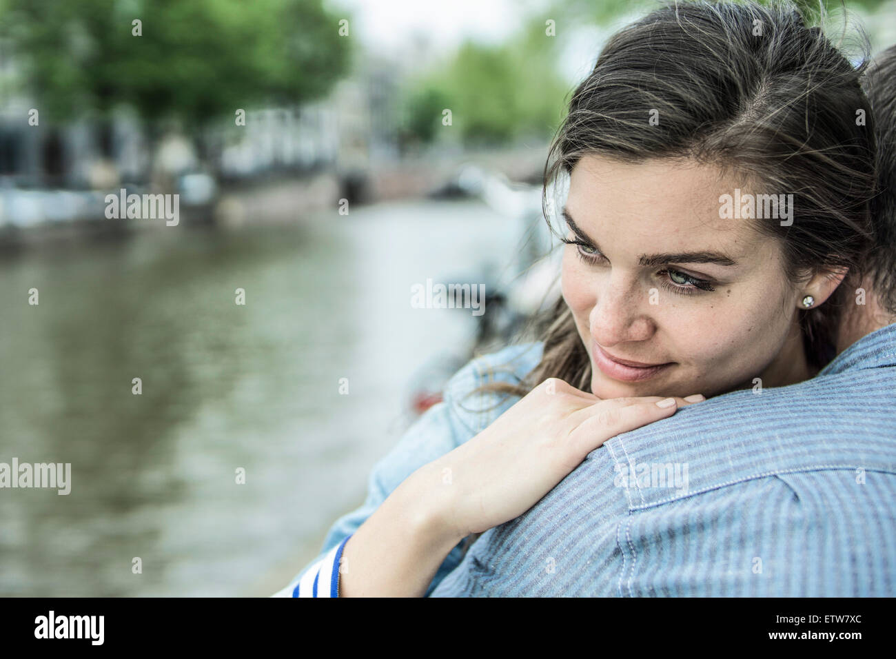 Netherlands, Amsterdam, woman embracing man in front of town canal - Stock Image