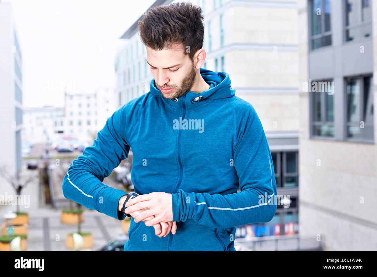Germany, Magdeburg, young man looking at his heart rate monitor - Stock Image